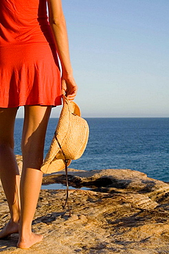 Woman holding a cowboy hat, standing next to the ocean, Sydney, Australia