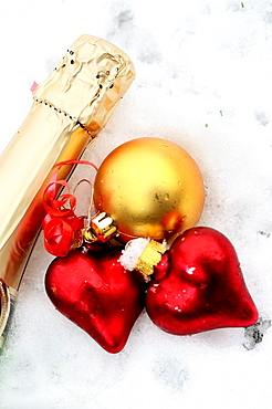 Two red satin glass hearts with champagne bottle neck and gold ball on snow