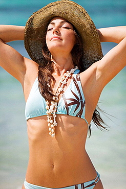 Young woman on the beach with hat on sunbathing.