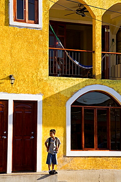 Young school boy standing in front of a brightly colored building in San Juan del Sur, Nicaragua