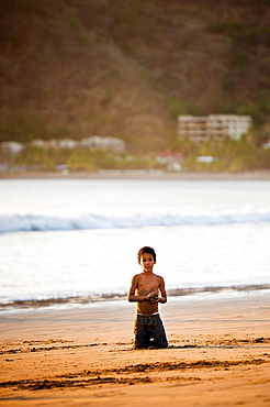 Little boy kneeling in the sand on the shore of San Juan del Sur, Nicaragua