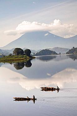 Dugout canoe floating on Lake Mutanda with the Virunga Vulcanoes in the background     Africa, East Africa, Uganda, Rwanda, Congo, Kigezi, Kisoro, February 2009