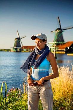 Portrait of a young woman and windmills  Zaanse Schans, Zaanstad,Zaandam, North Holland province, Holland, Netherlands, Europe
