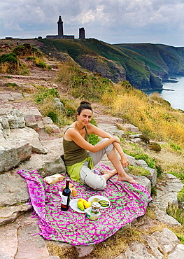 Young woman having a picnic in a cliff  Cape Frehel, Cancale, Ile-et-Vilaine, Brittany, France, Europe