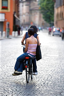 Two girls on a bicycle, Modena, Emilia-Romagna, Italy