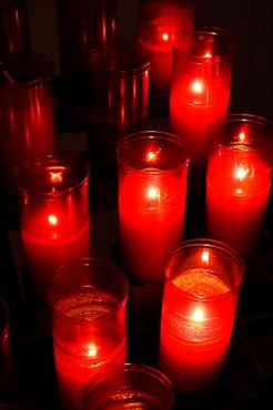 Velas encendidas en ofrenda en el interior de una iglesia