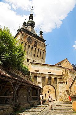 People walking the along the street in citadel beneath clock tower, Sighisoara, Transylvania, Romania