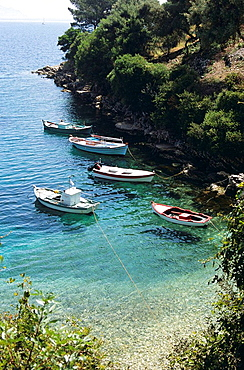 Fishing boats moored in natural cliff side harbour, Kioni, Ithaca, Greece