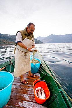 Fisherman at work on the lake, Iseo lake, Lombardia, Italy.