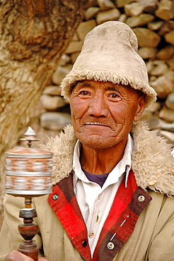 A happy tibetan man spinning a prayer wheel Alchi, Ladakh, India