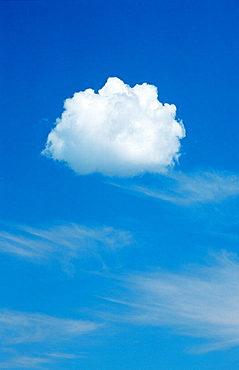 Small cumulus cloud against cirrus clouds and blue sky