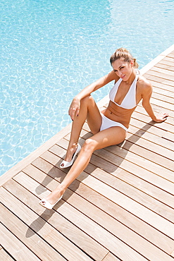 Sexy blonde woman with high heels by the pool