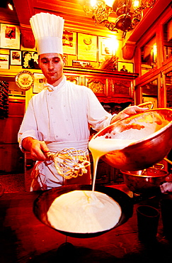 Restaurant 'La Mere Poulard': waiter preparing an omelette in front of customers, Mont St, Michel, Normandy, France