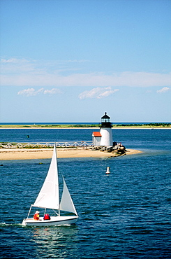 Sail boat leaving Nantucket Harbor off Cape Cod, Massachusetts, USA Passing Brant Point lighthouse at the harbor entrance