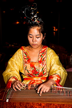 Chinese woman playing a stringed musical instrument, Xi'an, China