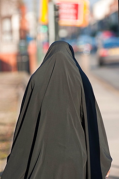 A Muslim woman wearing a Burka walks down Stoney Stanton Rd in Coventry, West Midlands, England
