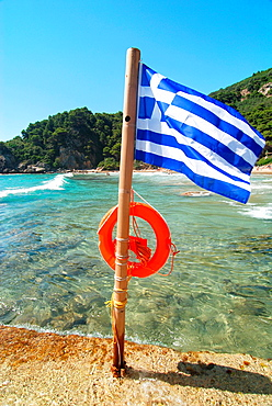 Greek flag with life belt, Ionian seashore near Sinarades town on green island of Crofu