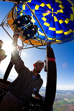 Santiago Valle, the pilot of the andalusian company of aerostatic ballons Glovento, acting on the burners to control the flying height over the plain of Antequera, Malaga, Andalusia, Spain