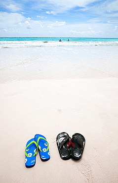 Barbados beach with a man and woman surfing and swimming in the Caribbean sea, and a pair of flip flops left on the beach.