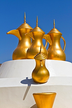 Decorative gold coffee urns at a roundabout in Muscat, Oman