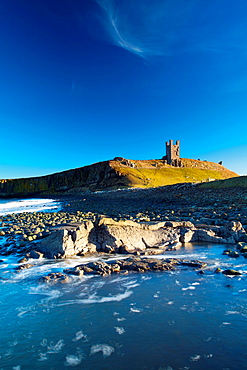England, Northumberland, Embleton Bay The Lilburn Tower, part of the remains of Dunstanburgh Castle, viewed from Embleton Bay