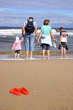family walking along a sandy beach