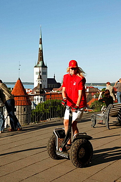 Girl riding segway in front of Lower Town City Wall Towers and St Olav Church, Unesco World Heritage, Old Town of The 13th Century Tallinn, Republic of Estonia, Eastern Europe.