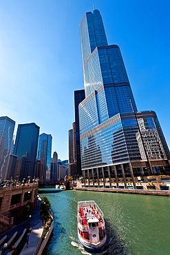 Chicago River boat passes the Trump International Hotel & Tower in Chicago, IL, USA