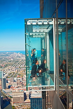 Tourists in the all glass balcony skydeck observation deck view the Chicago skyline103rd floor of the Willis Tower previously the Sears Tower