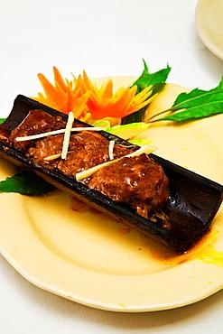 Grilled beef in bamboo Indochine Restaurant Hanoi Vietnam.