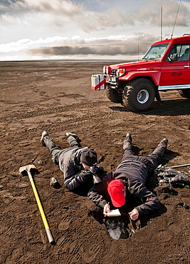 Scientist taking samples and measuring the ash fall from Grimsvotn volcanic eruption, Iceland  Team on ash covered glacier approx  35 kilometers from the crater The eruption began on May 21, 2011 spewing tons of ash