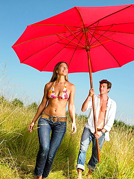 Couple with a beach umbrella in a field