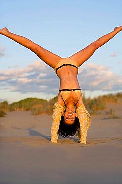Woman does cartwheel at beach