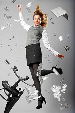 Woman jumping with office items, young business woman jumping with flying office objects