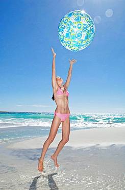 A girl playing with a beach ball, A portrait shot of a young girl jumping to catch a beach ball with the sea behind her