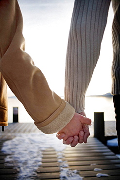 Hands holding on snowy pier