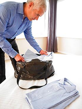 Man putting shirts in a bag, Man putting shirts in a bag