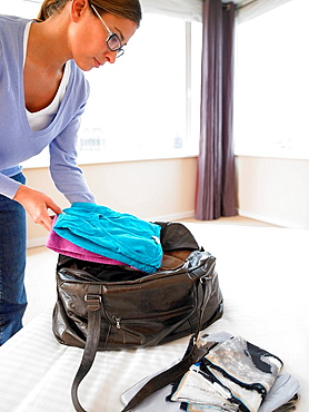 Woman putting clothes in a bag, Woman putting clothes in a bag