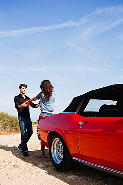 couple holding hands next to car