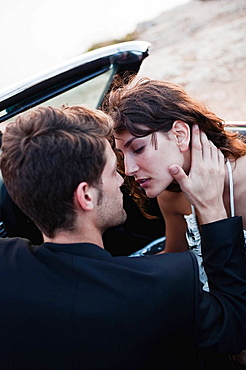 couple in car front seat kissing
