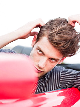 man looking into side mirror of car