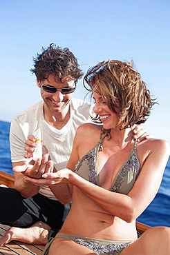 couple laughing applying suntan lotion