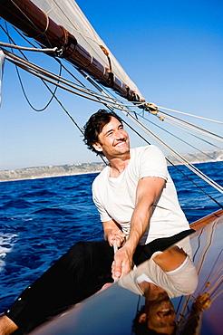 man smiling steering a sailing boat