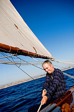 man smiling sitting on a sailing boat