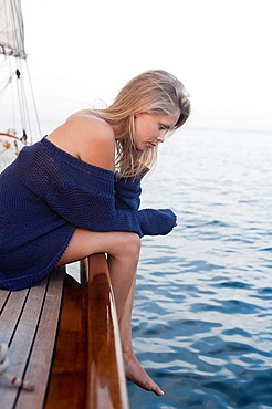 woman sitting on rail of a sailing boat