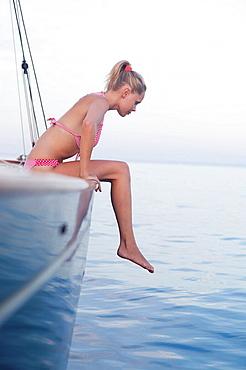 woman sitting on rail of sailing boat