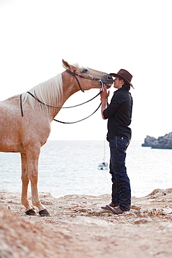 man kissing horse