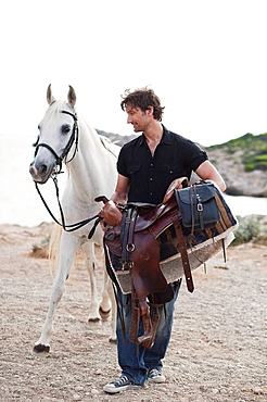 man carrying horses saddle