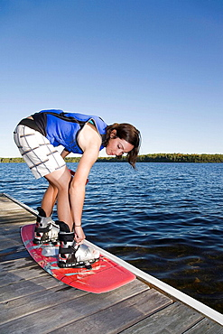 Woman strapping into wakeboard, Woman strapping into wakeboard