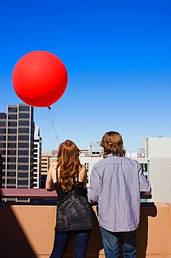 friends on roof top with red balloon